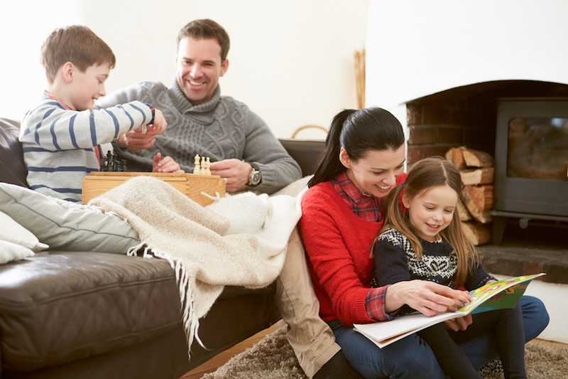 This family might need a new furnace. Family Relaxing Indoors Playing Chess And Reading Book Smiling